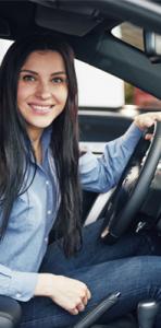 teen girl behind wheel of car